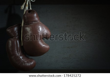 old used boxing Gloves, hanging before a dirty Wall - stock photo