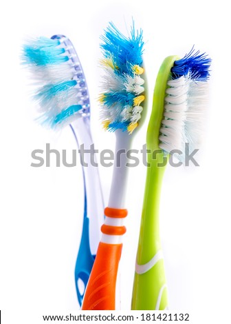 Old used colorful toothbrushes isolated on white background - stock photo