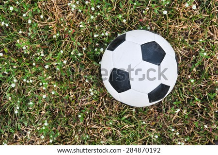 Old used football or old soccer ball on the ground - stock photo