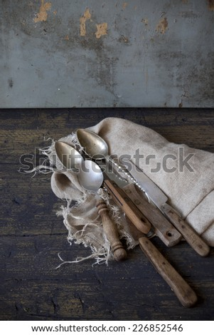 old used kitchen knives on frayed cloth on rustic scraped wooden table - stock photo