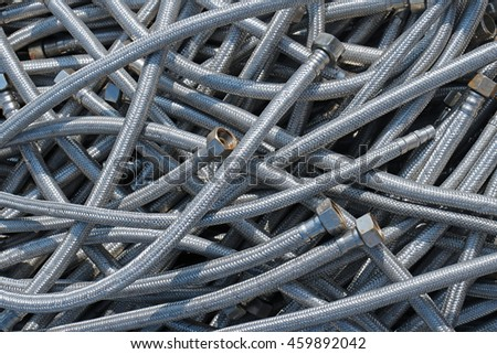 Old used silver rusty metal hoses pile