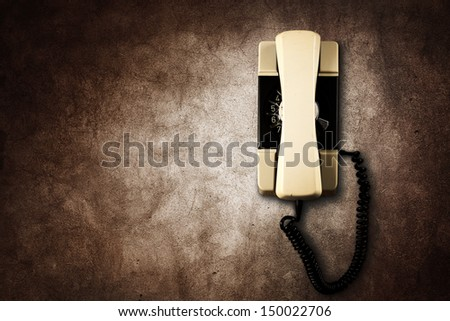 old used telephone on wall  - stock photo