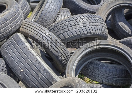 Old used tires stacked on the grass  - stock photo