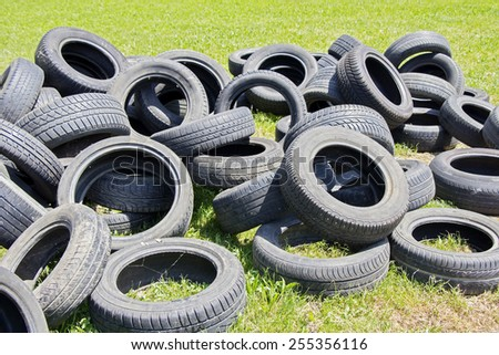 Old used tires stacked on the grass in the park  - stock photo