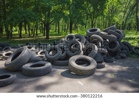 Old used tires stacked on the grass in the park
