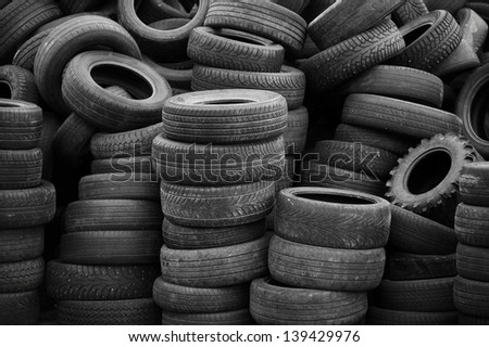 Old used tires stacked with high piles - stock photo