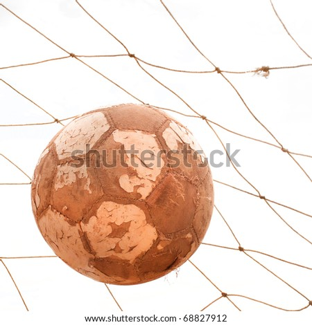 Old used vintage soccer ball in net. Goal. - stock photo