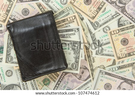 Old used wallet with dollars isolated on dollar bills - stock photo