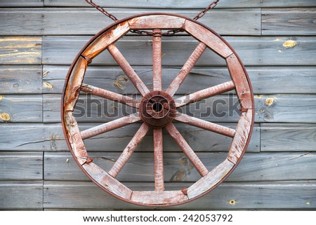Old used wooden wheel hanging on rural wall background - stock photo