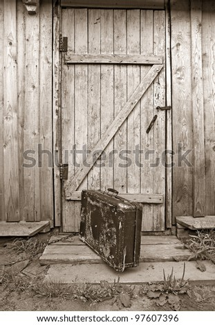 old valise near wooden door, sepia - stock photo