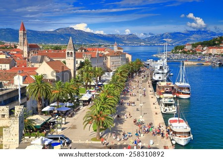 Old Venetian town along sunny pier and palm trees by the Adriatic sea, Trogir, Croatia - stock photo