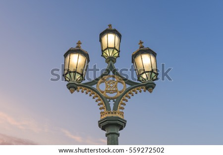 Old Victorian Light on the Westminster Bridge during warm winter sunrise, London, UK
