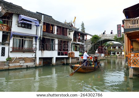 Old village by river in Shanghai with boat  - stock photo