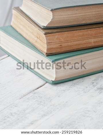 old vintage antique books pile on white wooden tabe - stock photo