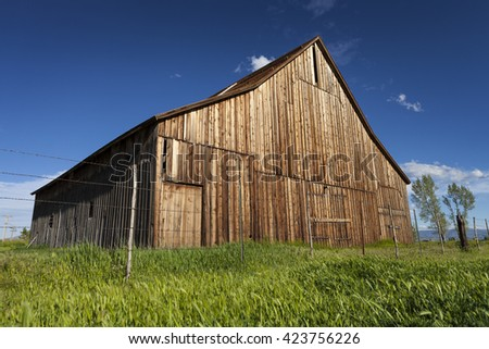 Old vintage barn on ranch with blue sky and green grass. - stock photo