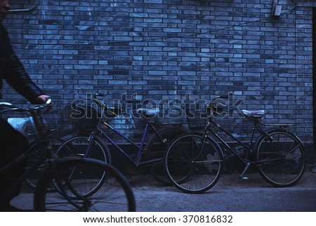 Old vintage bicycle near the brick wall an twilight  - stock photo