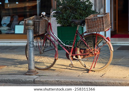 Old vintage bicycle with big basket on the street of old town Parma in Italy - stock photo