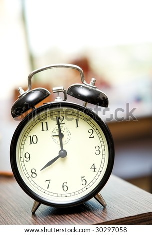 old vintage black alarm clock on table - stock photo