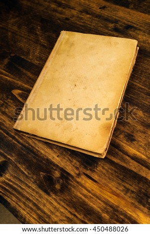 Old vintage book on rustic wooden table, blank covers as copy space, in perspective