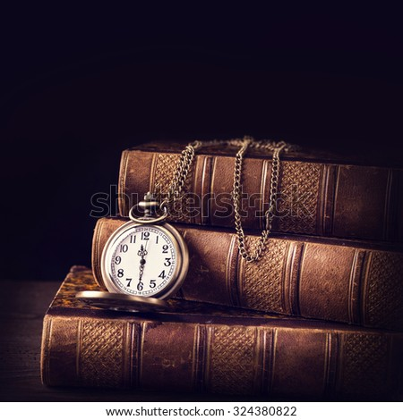 Old vintage books and a watch - stock photo