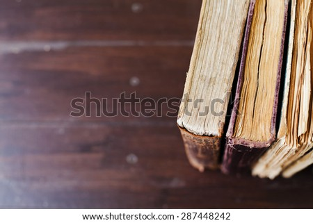 Old vintage books on dark wood background, selective focus and shallow dof