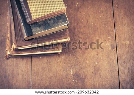 Old vintage books on wooden desk. Retro style filtered photo - stock photo