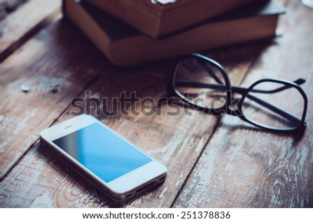 Old vintage books, smartphone and glasses on a wooden table - stock photo