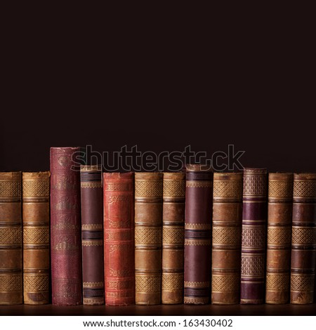 Old vintage books standing in a row - stock photo
