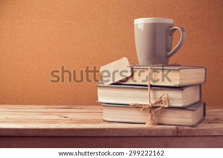 Old vintage books with cup and price tag on wooden table. Back to school concept - stock photo
