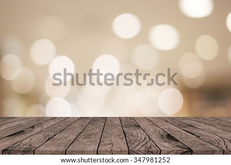 old vintage brown wood tabletop with blurred bokeh light sepia colored warm toned background:grunge aged wooden pave with blurry bulbs vintage backdrop.showing/advertising products on display picture - stock photo