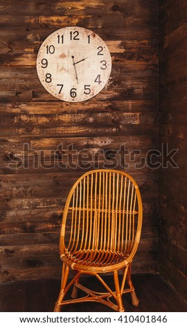 old vintage clock on a wooden wall,  wooden chair. - stock photo
