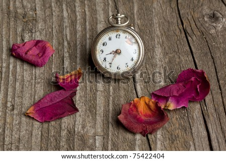 Old vintage clock with dry petals of rose on old wooden table - stock photo
