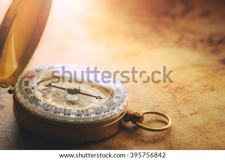 Old vintage compass on vintage map - stock photo