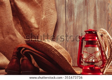 Old vintage cowboy tools - leather footwear, stetson, rope and kerosene lamp - stock photo