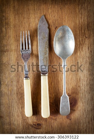 old vintage cutlery on a wooden table - stock photo