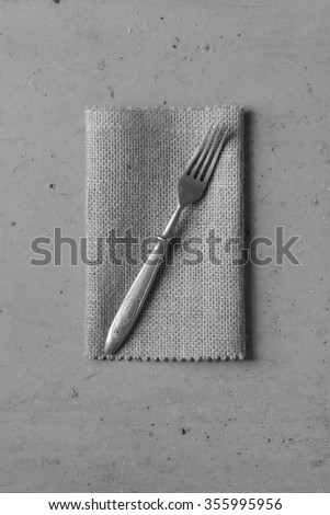 Old vintage fork on a linen napkin on a grey background. Top view. Black and white photo. - stock photo