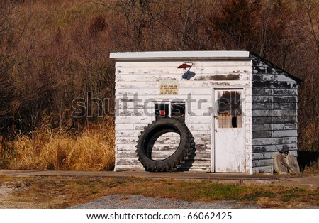 Old vintage gas house building with tire and peeled paint - stock photo