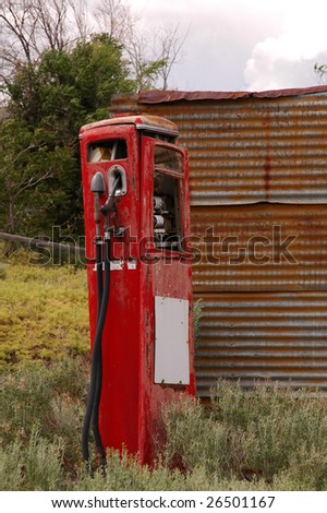 Old vintage gas pump next to shed