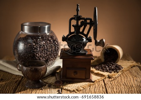 Old vintage grinder with roasted coffee beans .Dark still life