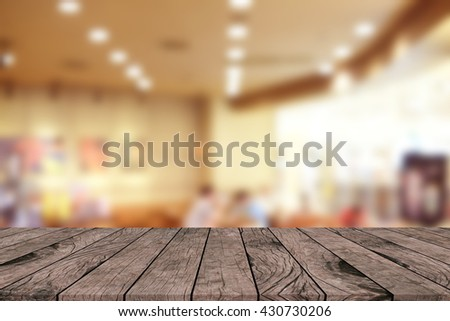 old vintage grungy brown wood tabletop with blurred restaurant bar cafe light color background:grunge aged wooden with blurry warm cream light bokeh backdrop.show/promote/advertise product on display - stock photo