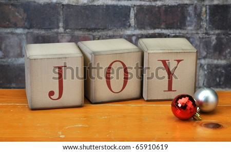 Old vintage holiday blocks spelling the word Joy with and ornaments - stock photo