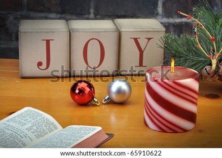 Old vintage holiday blocks spelling the word Joy with candle bible and ornaments - stock photo