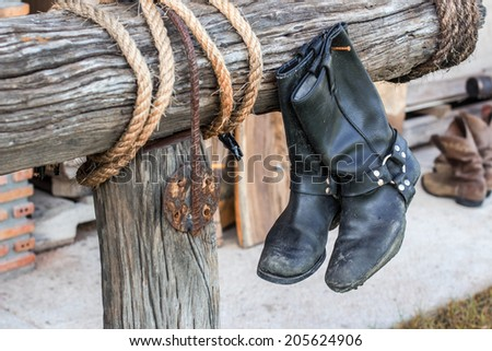 old vintage leather boots hang on the wooden wall - stock photo