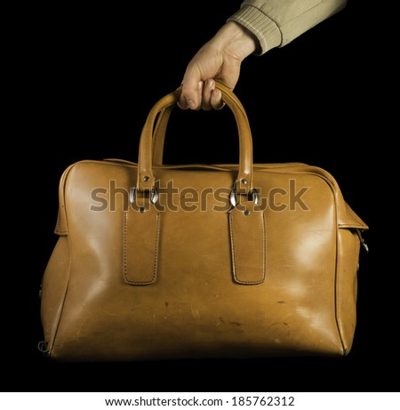 Old vintage luggage brown bag. Black isolated - stock photo
