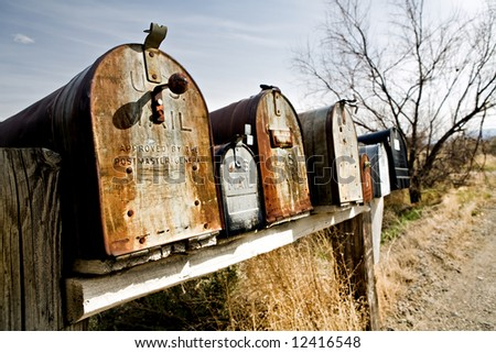 Old vintage mailboxes in rural Midwest United States, late sun - stock photo