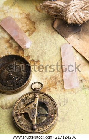 Old vintage maps with compass and pink quartz on it
