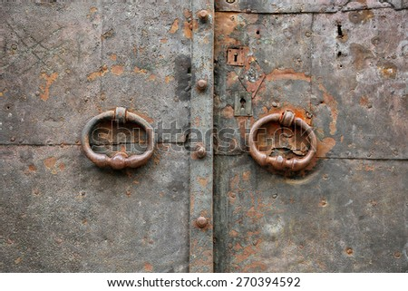 Old vintage metal door with ring handles and keyholes