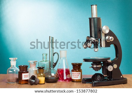 Old vintage microscope and laboratory glass bottles on table for science background - stock photo