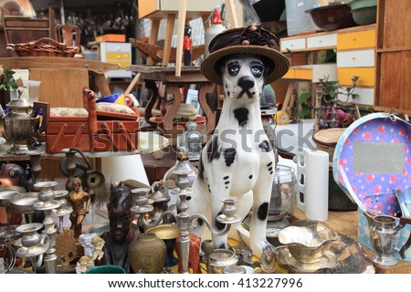 Old vintage objects and furniture for sale at a flea market. Toy vintage dog. Selective focus