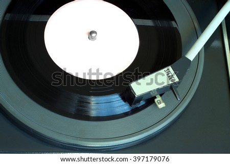 Old vintage record player playing vinyl record with pink label. Horizontal top view closeup - stock photo